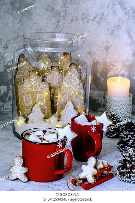 Cocoa in red cups with marshmelow, gingerbread men and gingerbread city in a glass jar in Christmas style