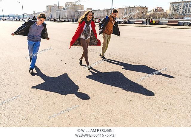 Russia, Moscow, group of friends having fun together and projecting airplane shaped shadows on the ground