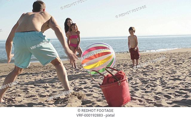 Family playing football with beach ball on beach