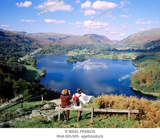 Couple resting on bench, viewing the lake at Grasmere, Lake District, Cumbria, England, UK