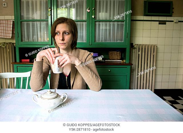 Tilburg, Netherlands. Adult caucasian woman drinking tea, while sitting at a vintage kitchen table