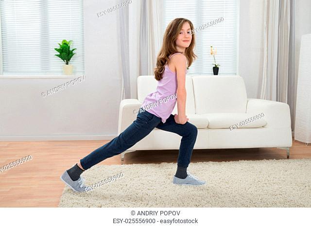 Girl In Sportswear Exercising In Living Room
