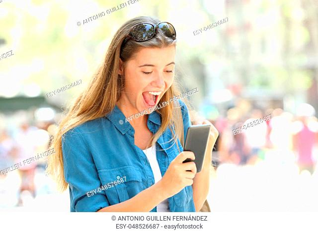 Excited girl reading good news holding a smart phone in the street