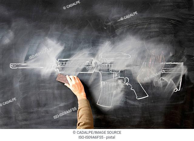 Person erasing chalk drawing of gun on blackboard