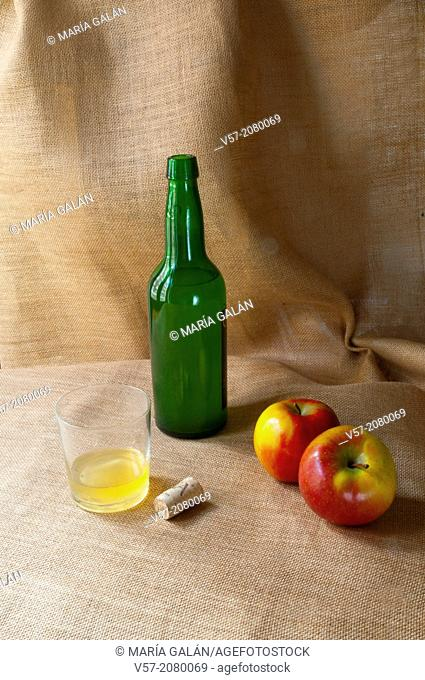 Asturian still life: bottle of cider, two apples, glass of cider and cork. Asturias, Spain