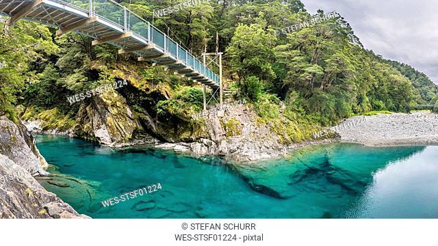 New Zealand, South Island, Mount Aspiring National Park, Blue pools at Makarora river with suspension bridge