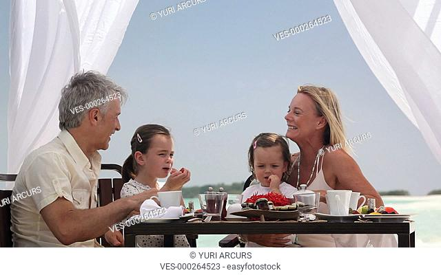 Two mature parents and their little girls enjoying a beach breakfast together