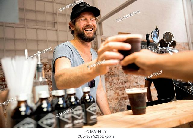 Male stall holder serving cold brew coffee on cooperative food market stall