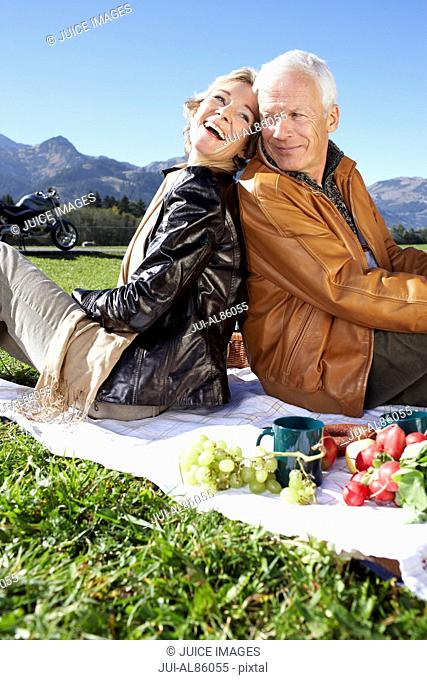 Senior couple having picnic with mountains in background