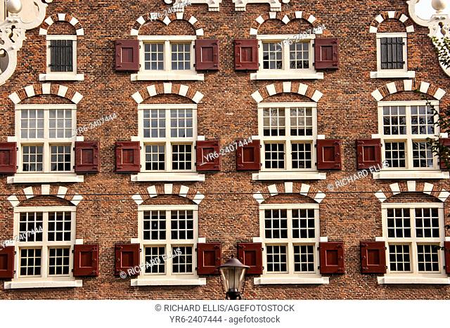 Facade of a brick building with decorative red shutters in Amsterdam