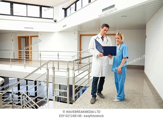 Nurse and doctor looking in folder in hospital