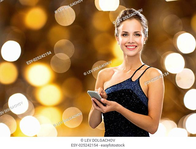 technology, smartphone, communication, people and holidays concept - smiling woman in evening dress texting on smartphone over lights background