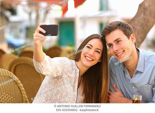 Happy couple taking a selfie photo with a smart phone in a restaurant terrace
