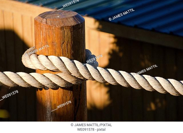 Close-up of heavyweight nautical rope secured to a dock