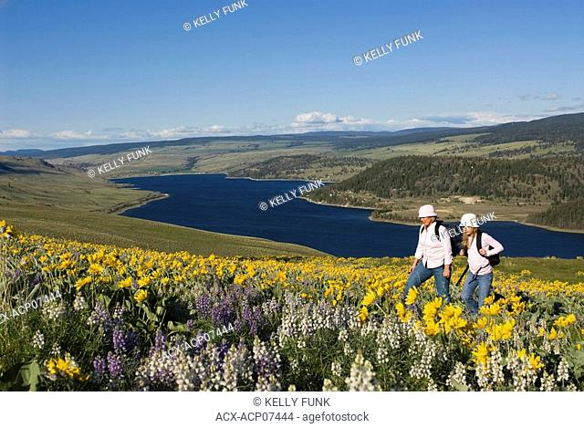 A young girl and her mother enjoy a beautiful spring day amidst the wildflowers over Stump Lake, near Kamloops, British Columbia, Canada