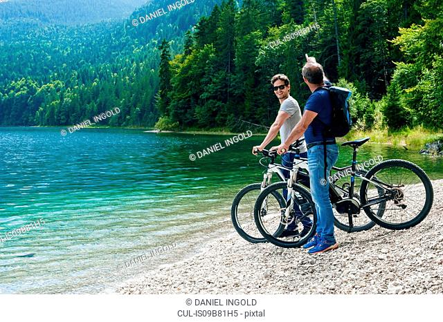 Father and adult son, standing beside lake with bicycles, looking at view, Elbsee, Bavaria, Germany