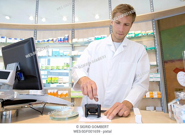 Young pharmacist stamping prescription