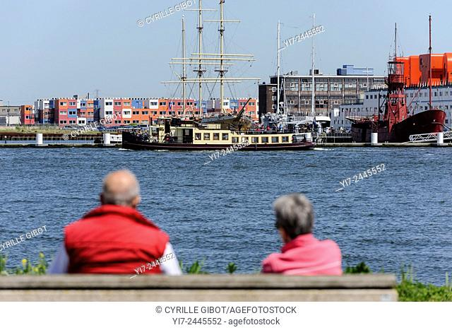 Senior couple watching boats on Ij river, Amsterdam, Netherlands