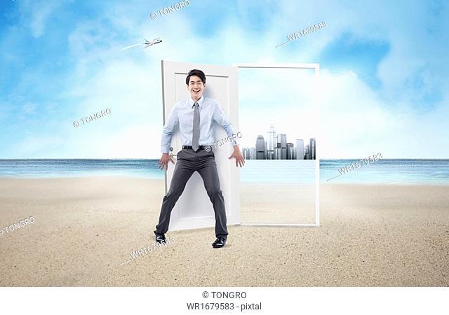 a business man standing on a beach next to a door