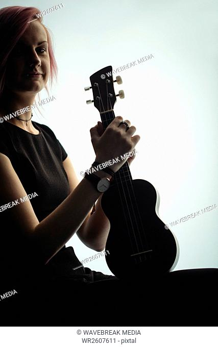 Woman sitting with a guitar in music school