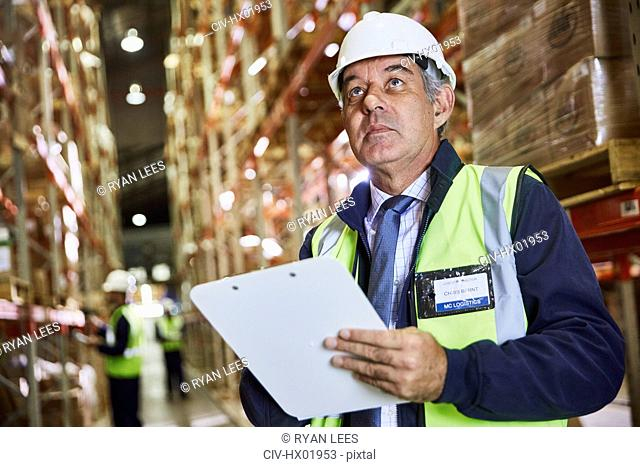 Manager with clipboard checking inventory looking up in distribution warehouse