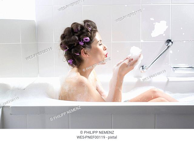 Young woman with curlers taking a bath