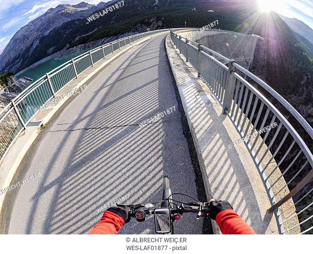 Italy, Lombardy, Sondrio, biker on dam wall of Cancano dam