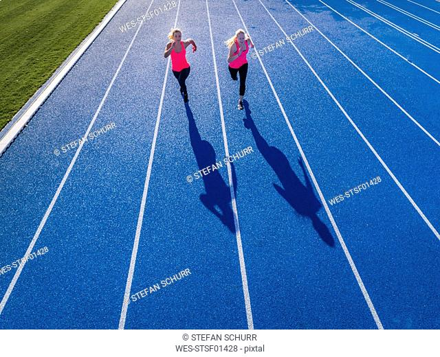 Aerial view of two female runners on tartan track