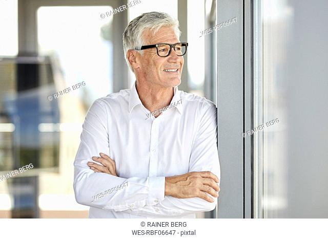 Businessman in office leaning against window, with arms crossed
