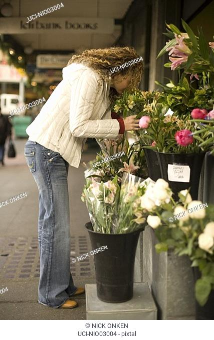 Young woman smelling flowers for sale