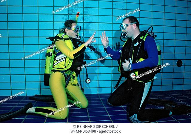 scuba diving lessons in a swimming pool giving OK signal, Munich Olympiabad, Germany