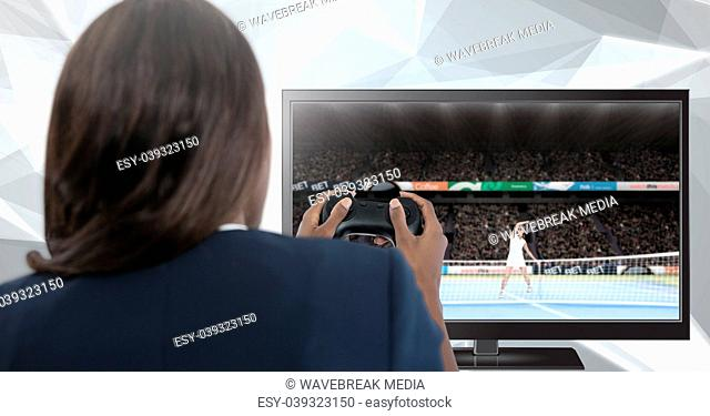 Woman holding gaming controller with tennis on television
