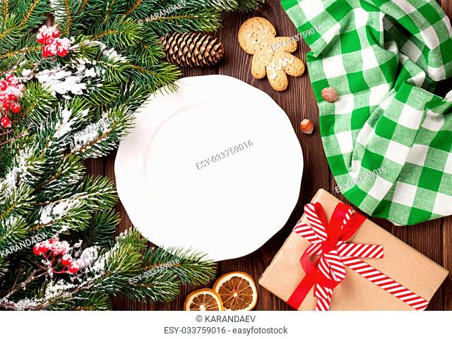 Christmas tree branch, empty plate and coffee. Top view with copy space