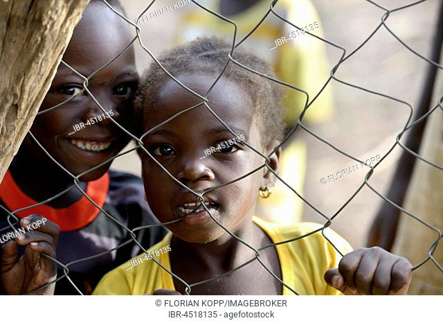 Two children looking through wire mesh fence, village Koungo, Plateau Central, Burkina Faso