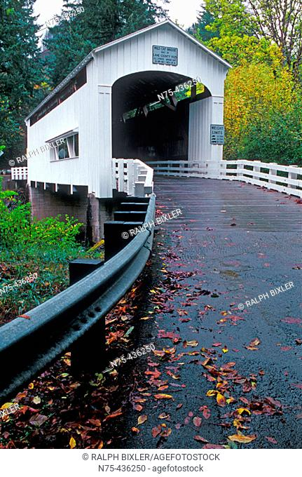 This bridge features decorative end brackets, ribbon openings under the eaves, wooden deck flooring and a side window. It is located in Lane County, Oregon