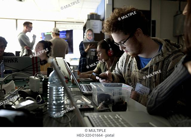 Hacker working hackathon at laptop and texting with cell phone in dark office