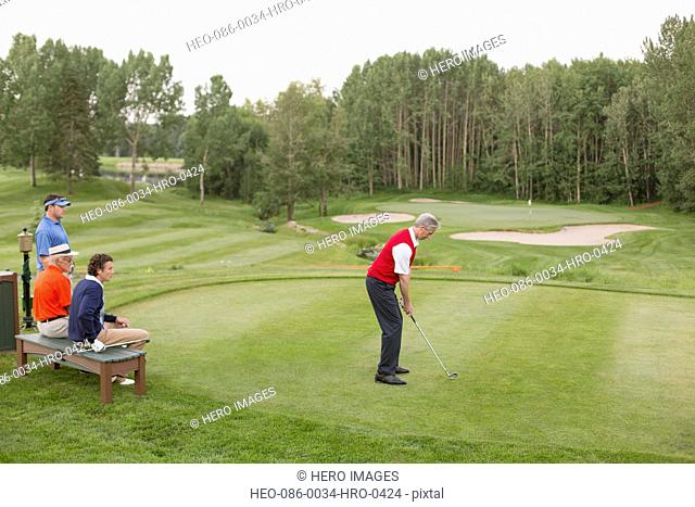 middle-aged male golfer ready to drive tee from tee-box