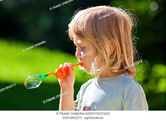 boy with long blond hair blowing sopa bubbles
