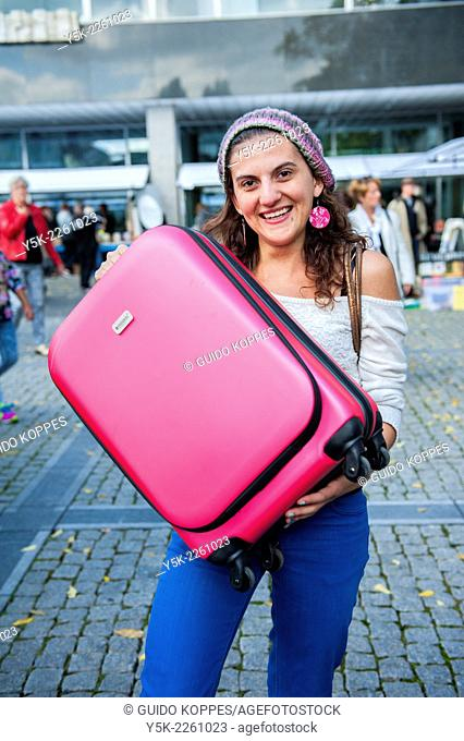 Tilburg, Netherlands. Young Italian woman showing her pink suitcase full of newly bought second hand book on the annual second hand book market