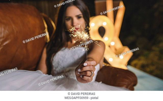 Close-up of sparkler in the hand of a bride lying on sofa on a night party outdoors
