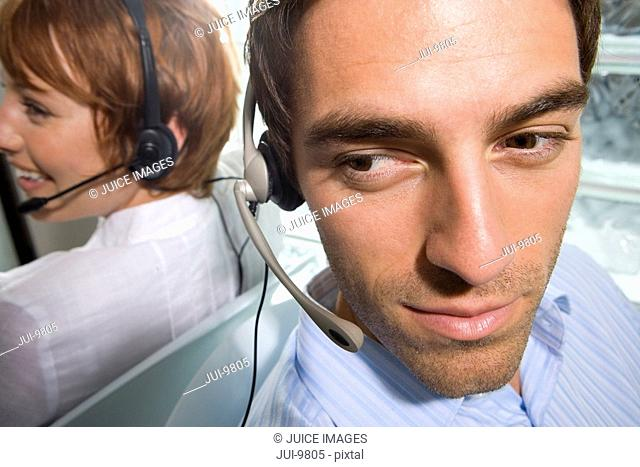 Businessman and woman wearing headsets sitting back to back, close-up, elevated view