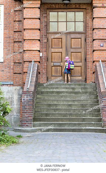 Back view of little girl with school bag in front of entrance of her school
