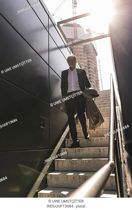 Mature businessman walking on staircase in the city