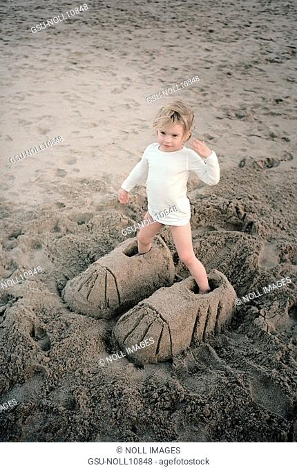 Young Girl Standing in Large Shoes Made in Sand