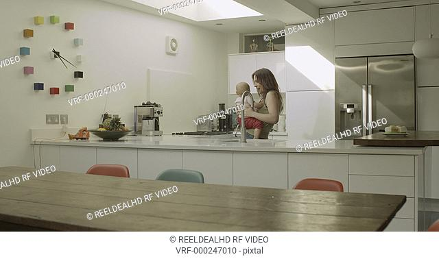 Mother playing with her daughter in kitchen
