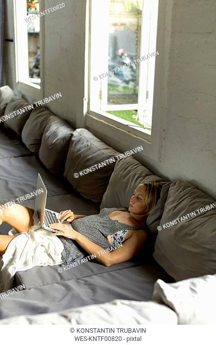 Blond woman lying on the couch using laptop