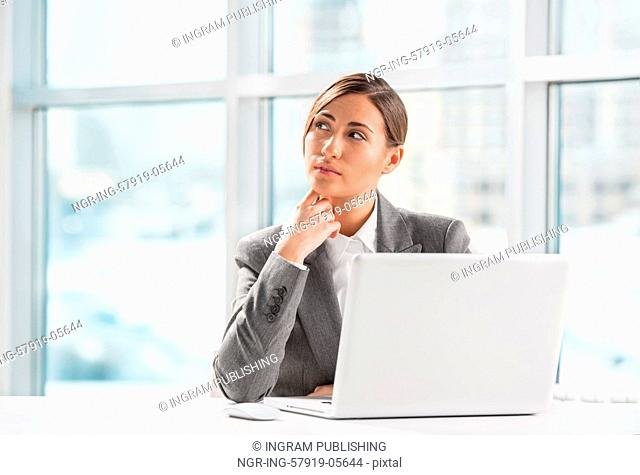 Portrait of business woman resting chin on hand in front of her laptop at office