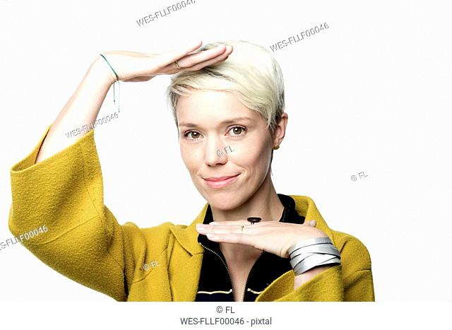 Portrait of smiling woman with short blond dyed hair gesturing in front of white background
