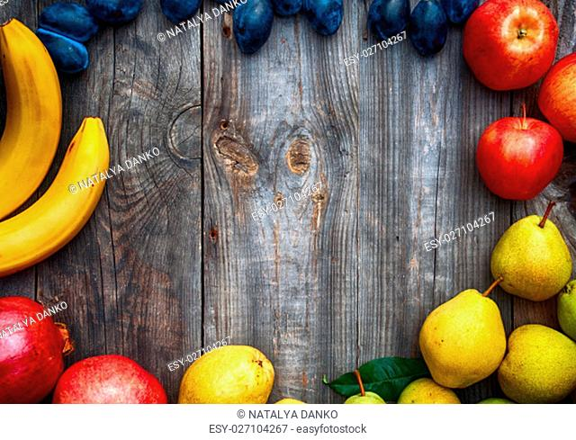 Ripe fruits lined frame on a gray wooden surface, empty space in the middle
