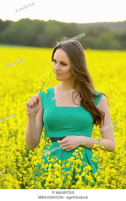 Young woman is standing in a rape field and smells in a blossom, looking into camera